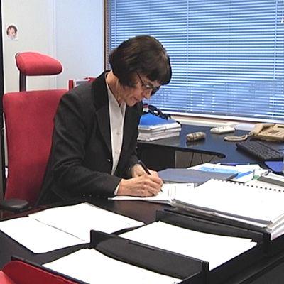 Kaija Holli allekirjoittaa paperia työpöytänsä äärellä.