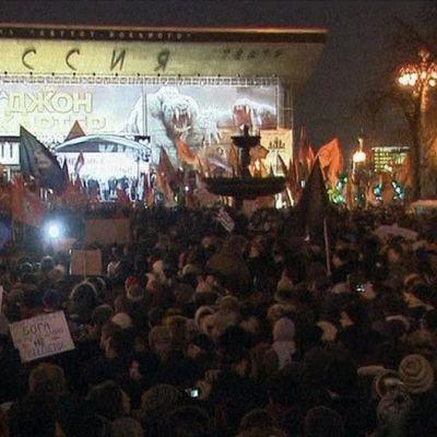 Mielenosoittajia lippuineen esiintymislavan edustalla