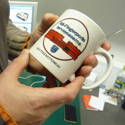 Kahvikuppi käsissä.