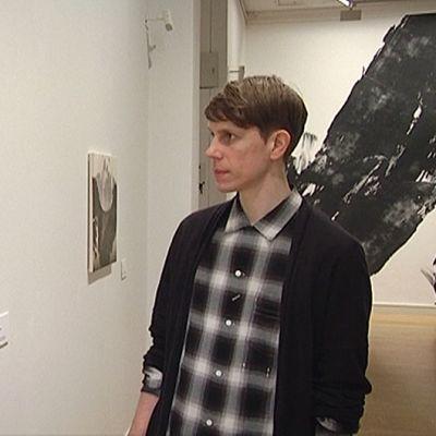 Ari Pelkonen katselee PYYHKÄISY-teosta.