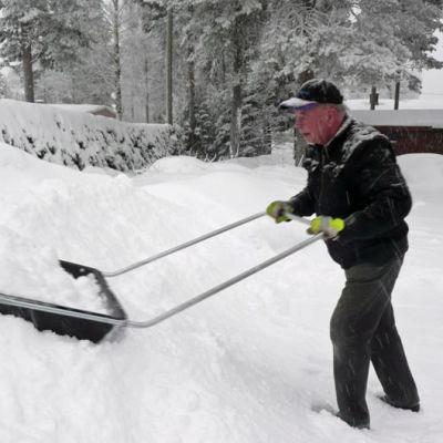 Mies kolaa lunta