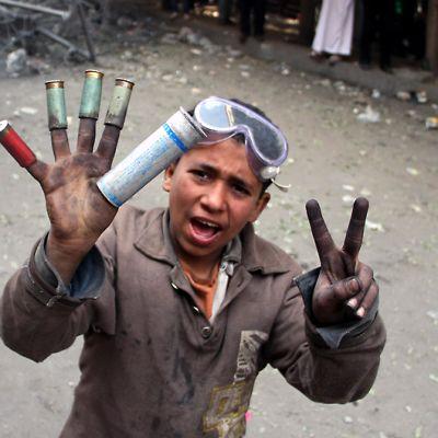 Nuori poika on laittanut oikean käden sormiinsa ammusten hylsyjä, jotka ovat erivärisiä.