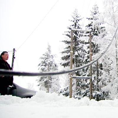 Raskaan lumen katkaisema sähkölinja maassa.