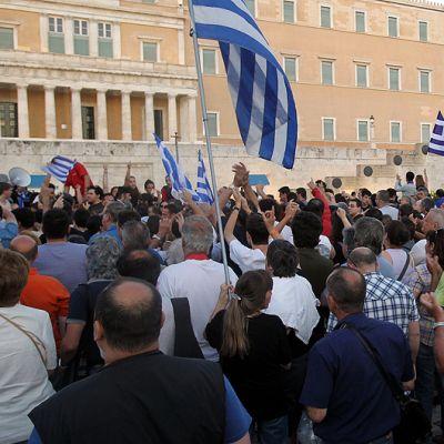 Säästöpakettia vastustavat mielenosoittajia Kreikan parlamentin edessä.