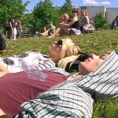 Koululaiset viettävät kesäpäivää nurmikolla.