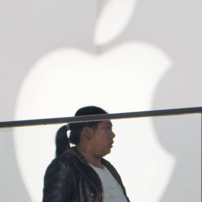 Nainen kävelee Applen Kiinan päämyymälän edustalla Pekingissä.
