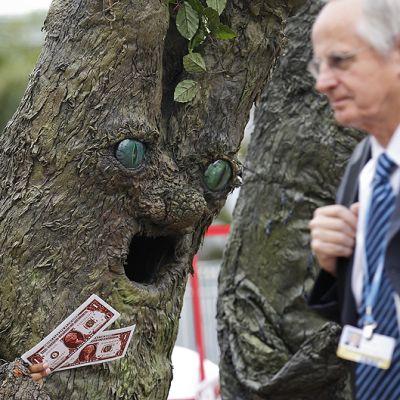 Puiksi pukeutuneet Greenpeacen aktivistit pyytävät ohikulkijoilta rahaa puille.