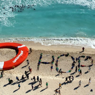 Ihmistet muodostavat sanan HOPE rannalla makaamalla muodostelmassa.