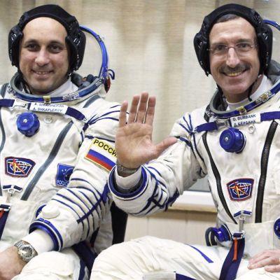 Astronautti ja kosmonautti hymyilevät ja vilkuttavat.