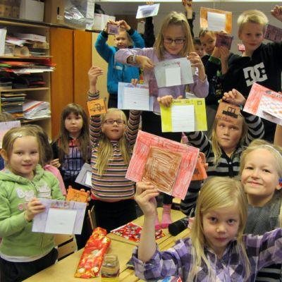 Koululaiset esittelevät isänpäivä kortteja ja -lahjoja