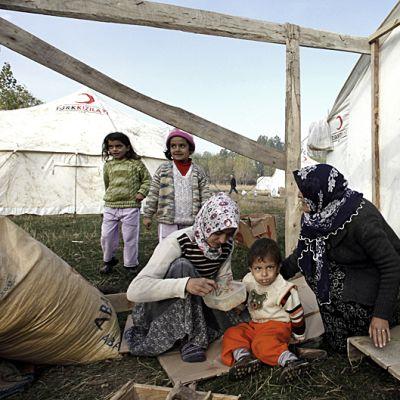 lapsiperhe pitää majaa telttojen välissä ja syöttää pientä poikaa
