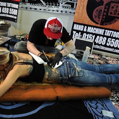 Tatuoija luonnostelee tatuointia asiakkaan alaselkään.