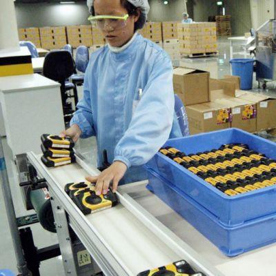 Työntekijä valmistaa kertakäyttökameroita Eastman Kodakin tehtailla Kiinassa, Xiamenissa vuonna 2004.