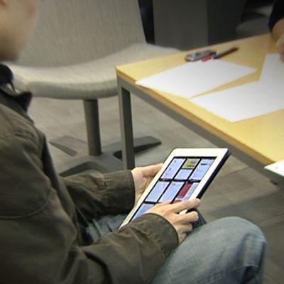 Opiskelija pitelee sylissään iPadia