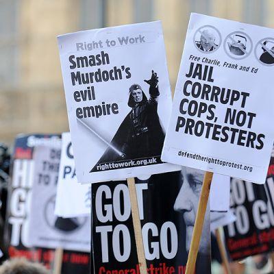 Mielenosoittajien Rupert Murdochia vastustavia ja pääministeri David Cameronin eroa vaativia kylttejä.