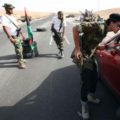 Libyan kapinallissotilaat tarkastavat autoja Tarhunan ja Bani Walidin välisellä maantiellä.