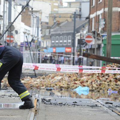 Palomies käärii vesiletkua palossa tuhoutuneen huonekalukaupan lähellä Lontoon Croydonissa.