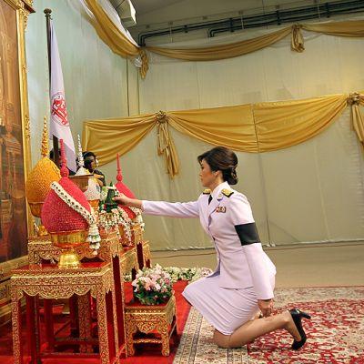 Thaimaan pääministeri Yingluck Shinawatra kunnioittaa virkaanastujaisseremoniassaan maan kuningasta polvistumalla tämän muotokuvan eteen.