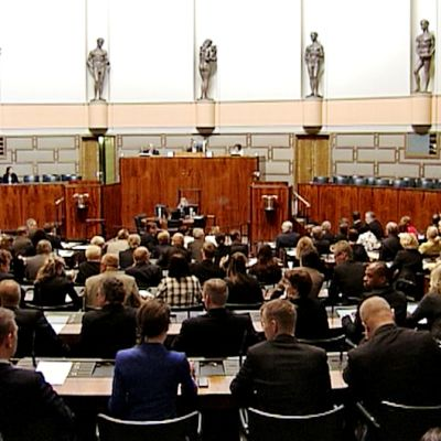 Kansanedustajat istuvat eduskuntasalissa äänestämässä.