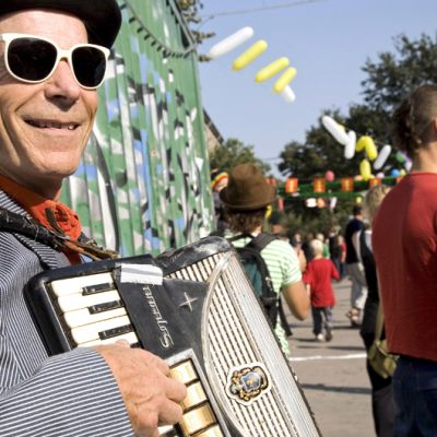 Mustahattuinen, liituraitaiseen pukuun pukeutunut mies soittelee haitaria kesäisen aurinkoisessa Christianiassa.