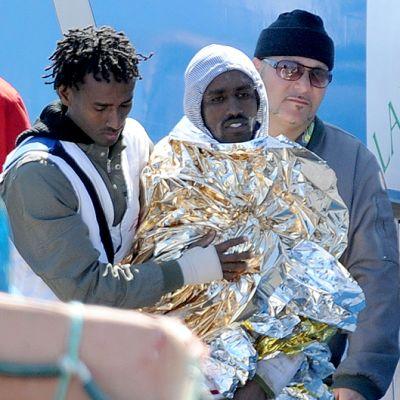 Kaatuneelta pakolaisia kuljettaneelta laivalta pelastunutta miestä talutetaan ensiapuun.