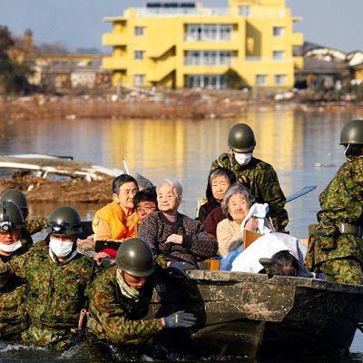 Sotilaat auttavat ihmisiä turvaan veneellä.