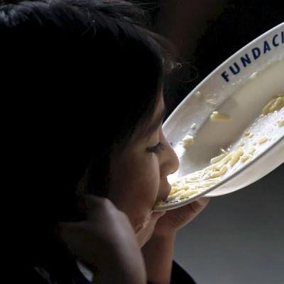 Nuori mustahiuksinen tyttö syö valkoiselta lautaselta.