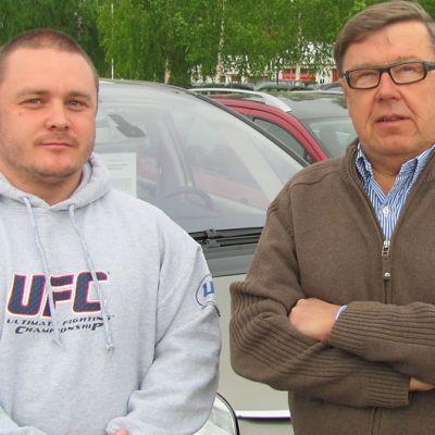 Kaksi miestä myytävien autojen edessä