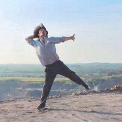 Mies tanssi kielekkeellä, hiekkaisella maaperällä.