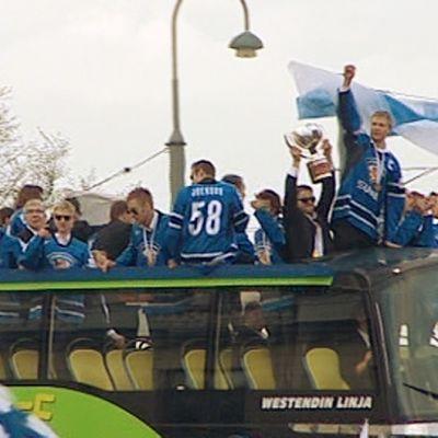 Maailmanmestarijoukkue saapuu Helsingin Kauppatorille kaksikerroksisella bussilla.