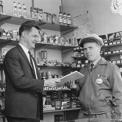 Mustavalkokuva vuodelta 1965. Mies Esson lakissa saa kunniakirjan kahdelta pukumieheltä.