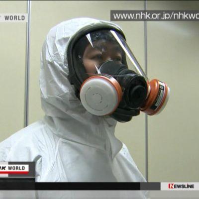 Japanilainen ydinvoimalatyöntekijä suojapuvussa