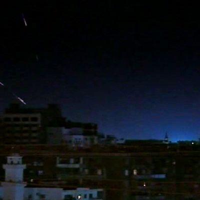 Öinen kaupunkikuva, ammusten valojuovia taivaalla.