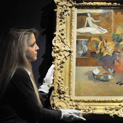 Huutokauppa Christie'sin työntekijä esittelee  Paul Gauguinin teosta Nature morte a 'L'Esperance.