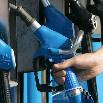 Mies on nostamassa bensiinipistoolia telineestä tankkausta varten.
