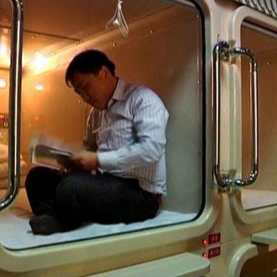Mies istuu kapselihotellin kapselissa.