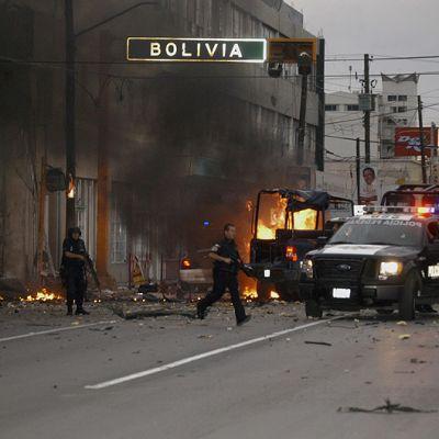 Poliiseja ja palava auto kadulla.