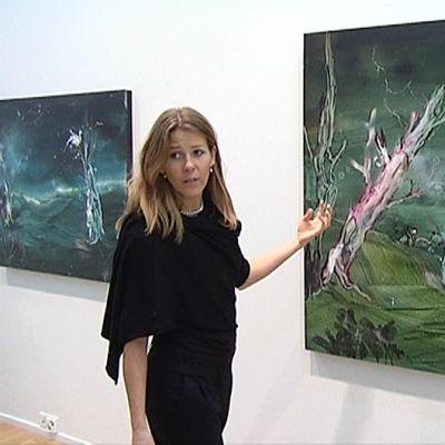 Anna Tuori kertoo maalaustekniikastaan taulun edessä.