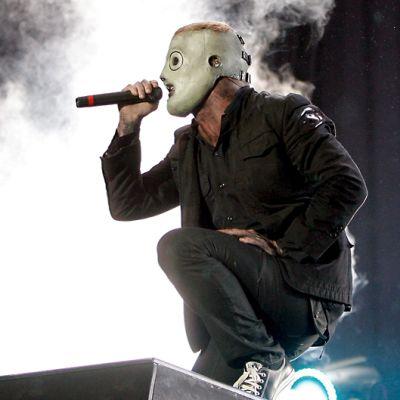 Laulajalla on harmaa maski päässään, takaa nousee savusumua.