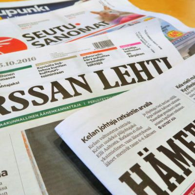 Sanomalehtiä pöydällä