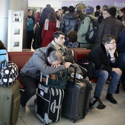 Matkustajia odottelee laukkuineen rusehtavan punaisella sohvalla.