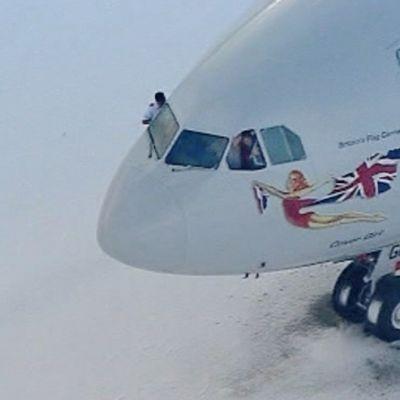 Lentokone lumisella kentällä. Ohjaamon ikkunoista vilkutellaan.