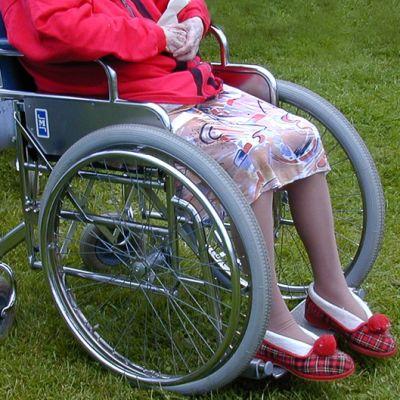 Iäkäs nainen istuu pyörätuolissa