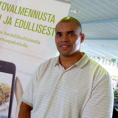 mies julisteen vieressä, teksti Ravintovalmennusta helposti ja edullisesti, julisteessa kuva kännykästä, jossa kuva ruoka-annoksesta