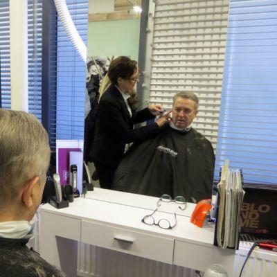 Kampaaja Tanja Iisalo leikkaa Pekka Peurasaaren hiuksia.