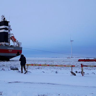 Laivaa hinataan jäiden keskellä satamassa.