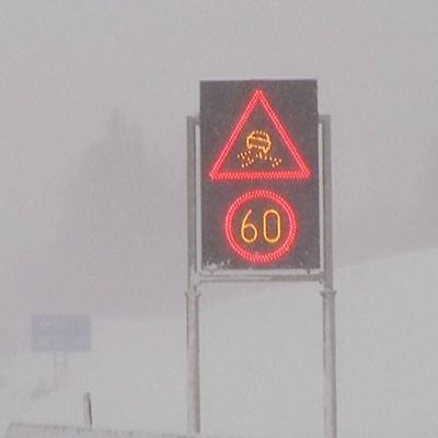 Digitaalinen näyttötaulu moottoritiellä. Näytössä on 60 kilometrin nopeusrajoitus ja huonon ajokelin symboli. Sataa rajusti lunta ja lumi pöllyää peittäen näkyvyyden.