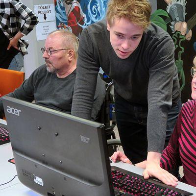 Nuori mies opastaa vanhempaa naista tietokoneen äärellä