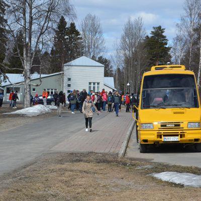 Koululaisia kävelemässä koulukuljetuksen kyytiin Simon Asemakylän koululla.