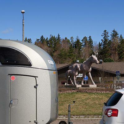 Ypäjän keskustan hevospatsas, etualalla farmariauton vetämä hevoskuljetusvaunu